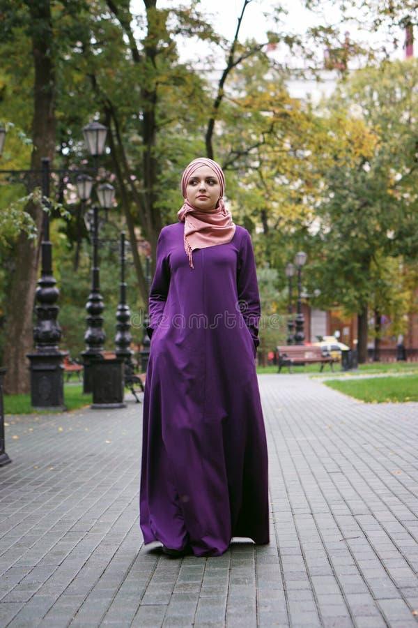 Piękna Muzułmańska kobieta w nowożytnym Islamskim smokingowym spacerze w miasto parku zdjęcia royalty free
