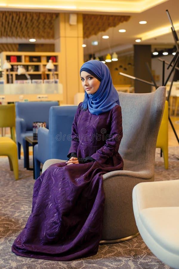 Piękna muzułmańska kobieta w nowożytnym orientalnym odzieżowym obsiadaniu w krześle w lobby zdjęcie stock