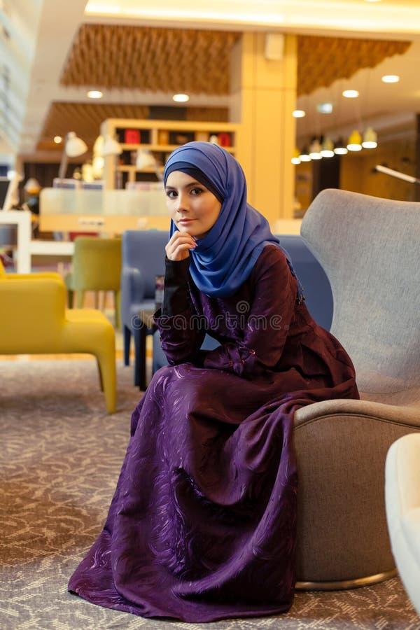 Piękna muzułmańska kobieta w nowożytnym orientalnym odzieżowym obsiadaniu w krześle w lobby obrazy stock