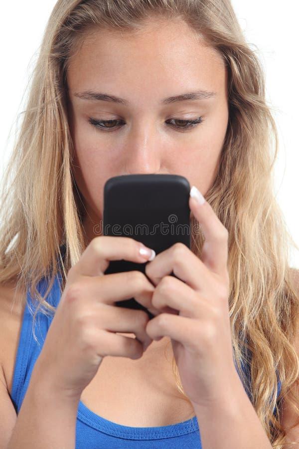 Piękna nastolatek dziewczyna koncentrująca w jej telefonie komórkowym obraz royalty free