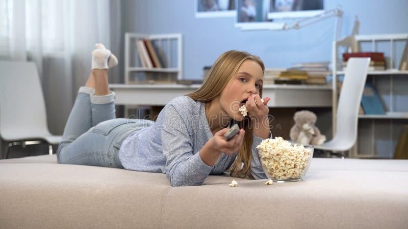 Piękna nastolatek dziewczyna ogląda tv i je wystrzał kukurudzy, rozrywka czas zdjęcia royalty free