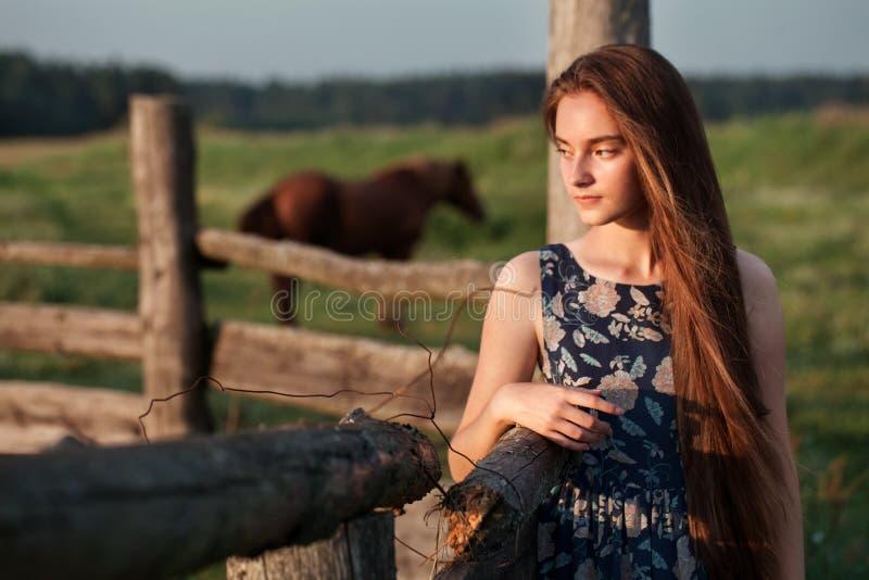 Piękna nastolatek dziewczyna relaksuje na zmierzchu wieczór w gospodarstwie rolnym na lato czasie z długim zdrowym włosy w błękit zdjęcie stock