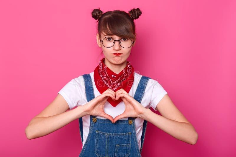 Piękna nastolatek dziewczyna robi kształtowi serce z jej rękami na różowym tle Gest miłość ładnym młodym uczniem, patrzeje obraz stock