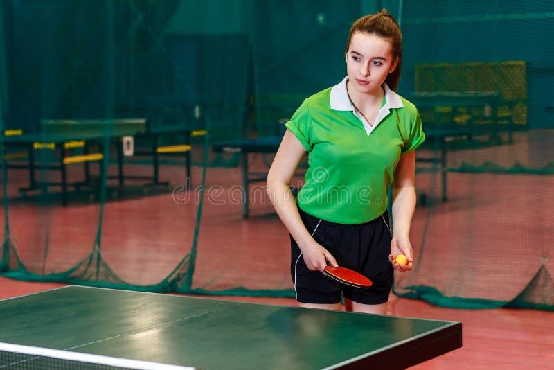 Piękna nastolatek dziewczyna w sport formie robi serw w stołowym tenisie w gym balowego b??kitny paddle ?wista pong nieba sto?owy zdjęcia royalty free