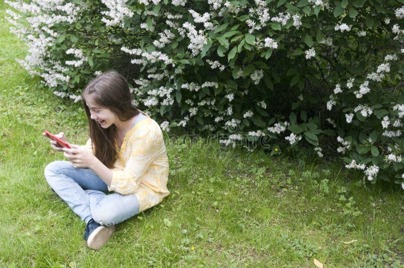 Piękna nastolatek dziewczyna z pastylka komputerem siedzi na trawie w parku fotografia obraz stock