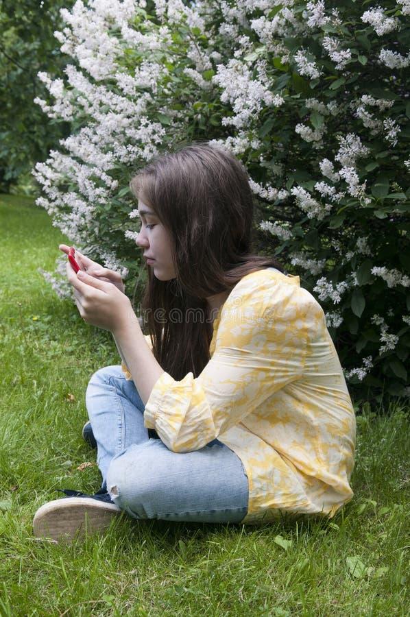 Piękna nastolatek dziewczyna z pastylka komputerem siedzi na trawie w parku fotografia obrazy royalty free