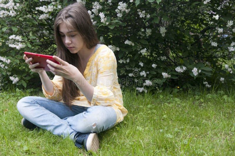 Piękna nastolatek dziewczyna z pastylka komputerem siedzi na trawie w parku fotografia fotografia stock
