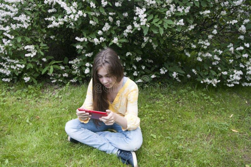 Piękna nastolatek dziewczyna z pastylka komputerem siedzi na trawie w parku fotografia zdjęcia royalty free