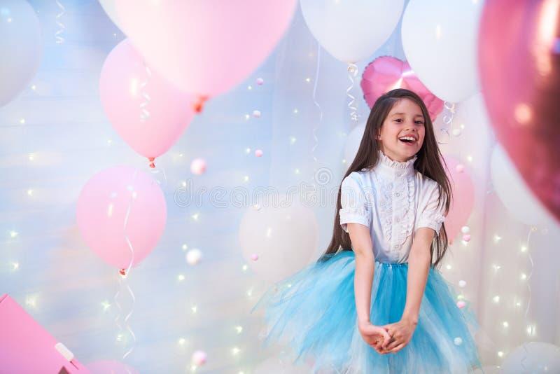 Piękna nastoletnia dziewczyna śpiewa piosenkę w scenerii balony folii i lateksu balony wypełniający z helem obraz stock
