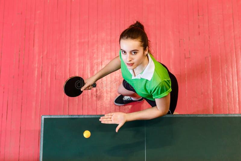 Piękna nastoletnia dziewczyna bawić się piłkę w stołowym tenisie Wiek dojrzewania i ?wista pong obraz royalty free