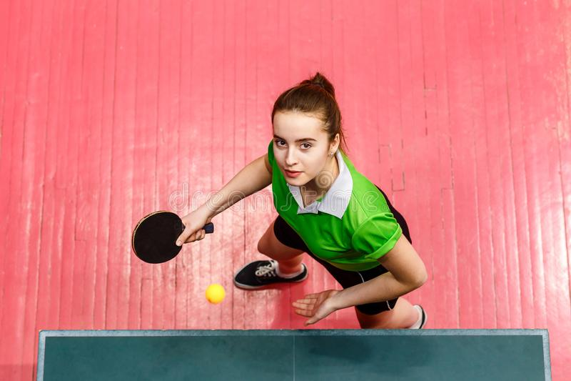 Piękna nastoletnia dziewczyna robi serw w stołowym tenisie, odgórny widok Wiek dojrzewania i ?wista pong obrazy royalty free