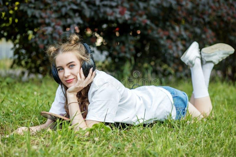 Piękna nastoletnia dziewczyna słucha piosenki z hełmofonami w parku Pojęcie styl życia, czas wolny zdjęcia stock