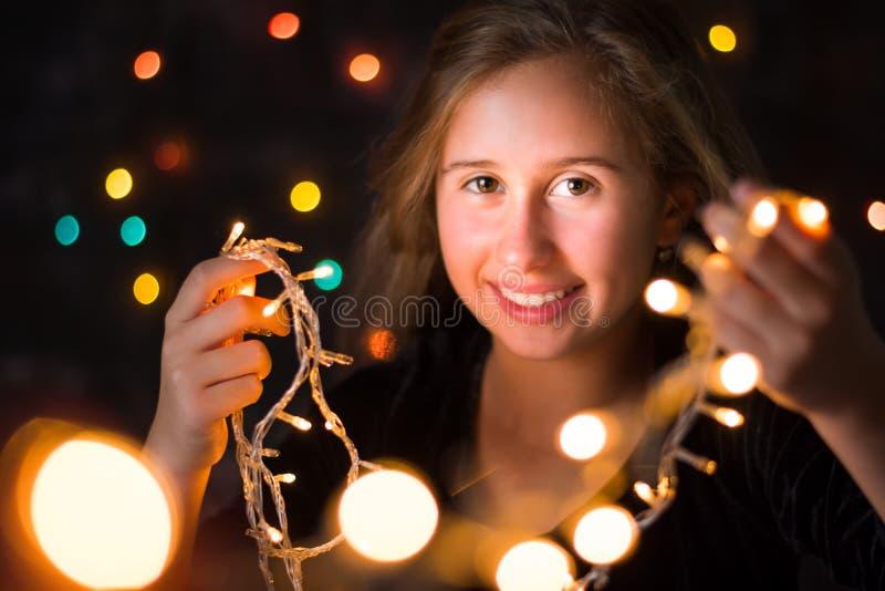 Piękna nastoletnia dziewczyna trzyma świątecznych światła obraz royalty free