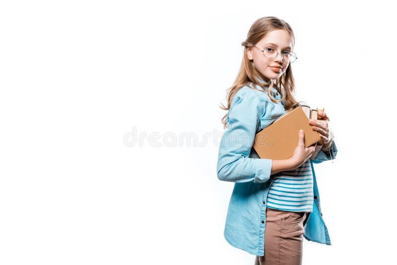 Piękna nastoletnia dziewczyna trzyma książki i ono uśmiecha się przy kamerą w eyeglasses obraz royalty free