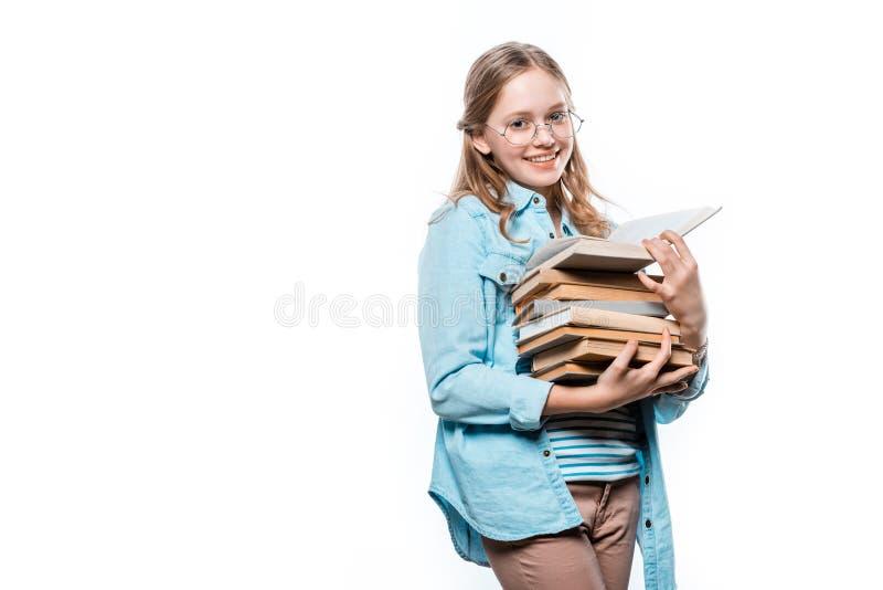 Piękna nastoletnia dziewczyna trzyma stertę książki i ono uśmiecha się przy kamerą w eyeglasses zdjęcia stock