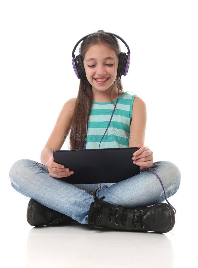 Piękna nastoletnia dziewczyna używa pastylka komputer zdjęcia stock