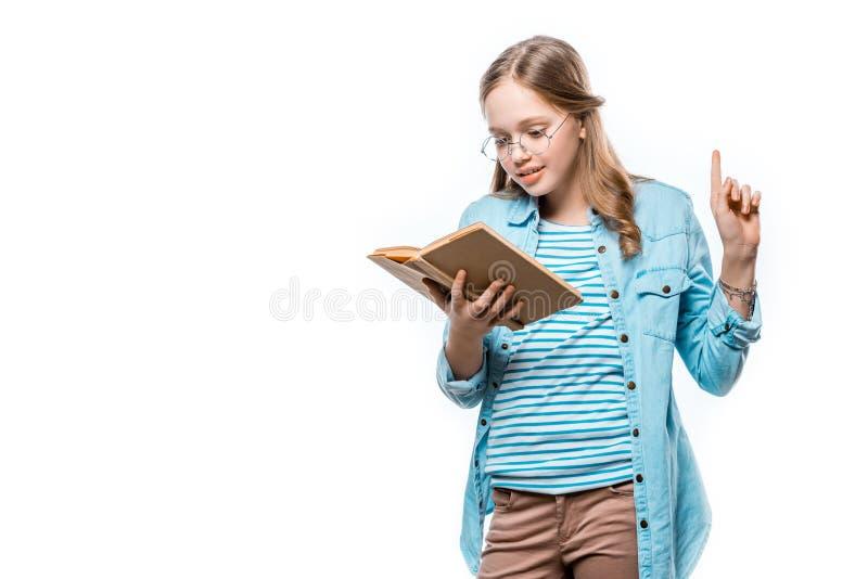 Piękna nastoletnia dziewczyna w eyeglasses czytelniczej książce i wskazywać up z palcem obrazy stock
