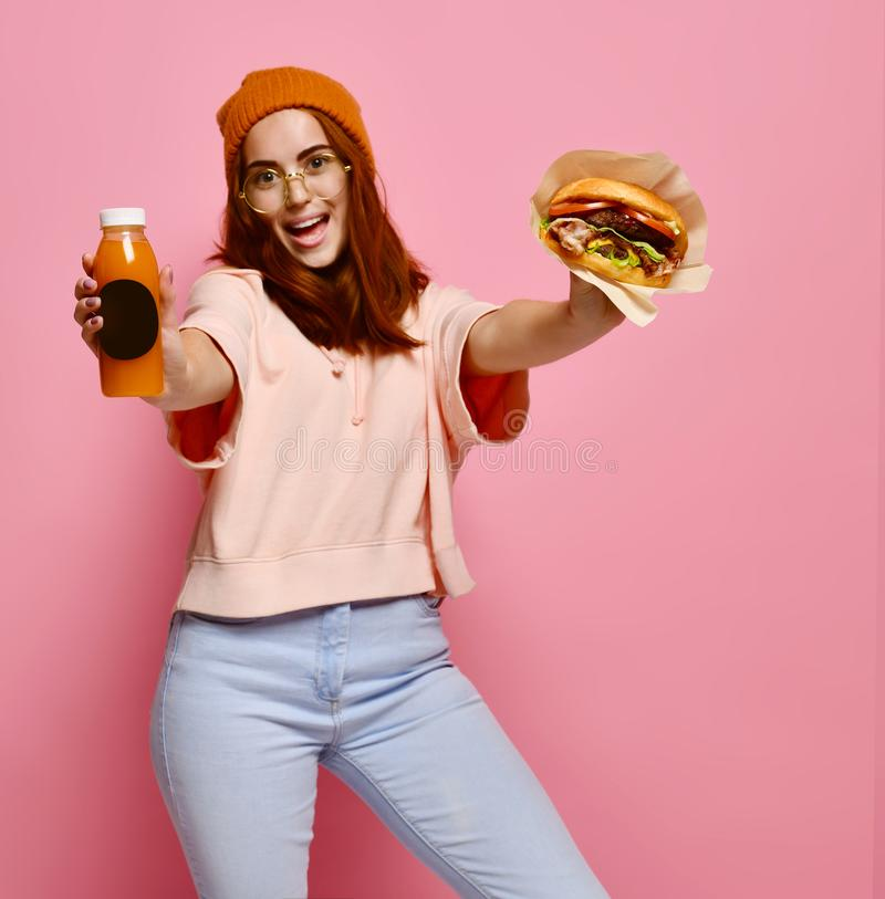 Piękna nastoletnia dziewczyna z czerwonym mienie hamburgerem, napojem w oba rękach włosy i kapeluszu i obrazy royalty free
