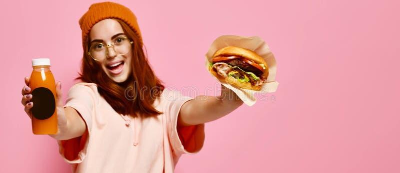 Piękna nastoletnia dziewczyna z czerwonym mienie hamburgerem, napojem w oba rękach włosy i kapeluszu i zdjęcie royalty free