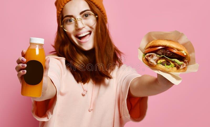 Piękna nastoletnia dziewczyna z czerwonym mienie hamburgerem, napojem w oba rękach włosy i kapeluszu i fotografia stock