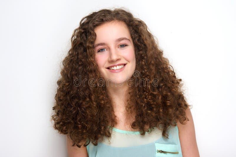 Piękna nastoletnia dziewczyna z kędzierzawego włosy ono uśmiecha się zdjęcie royalty free