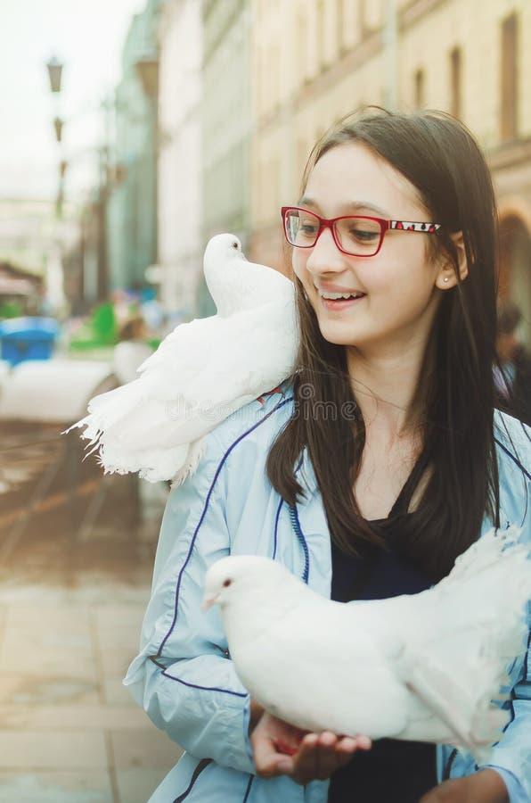 Piękna nastoletnia dziewczyna z szkłami śmia się i spojrzenia przy białą gołąbką umieszczającą obrazy stock