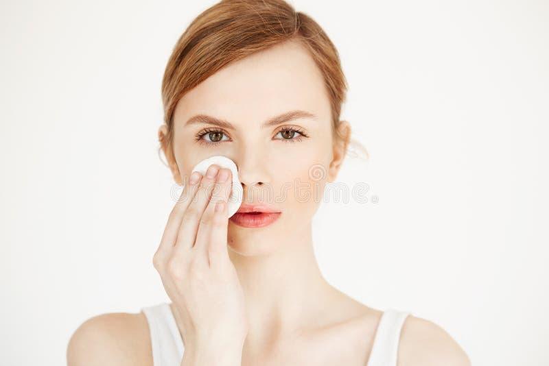 Piękna naturalna blondynki dziewczyny cleaning twarz z bawełnianą gąbką patrzeje kamerę nad białym tłem Kosmetologia i zdjęcia royalty free