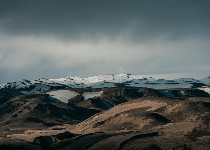 Piękna naturalna sceneria z śnieżnymi wzgórzami i zmroku popielatym niebem obraz royalty free