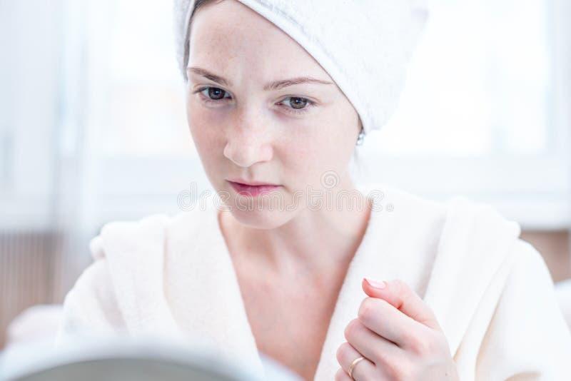 Piękna nieszczęśliwa młoda kobieta z ręcznikiem na jej głowie patrzeje jej skórę w lustrze Higiena i opieka dla skóry fotografia royalty free