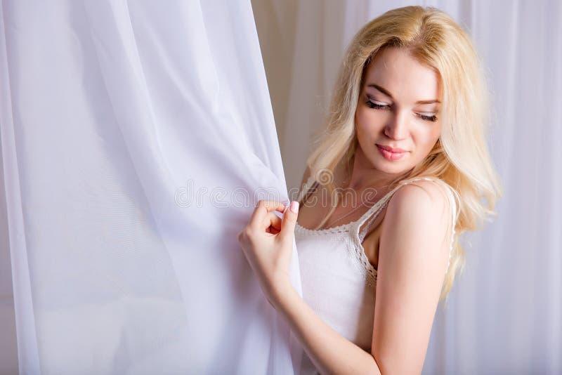 Piękna nikła blond dziewczyna pozuje na łóżku fotografia royalty free