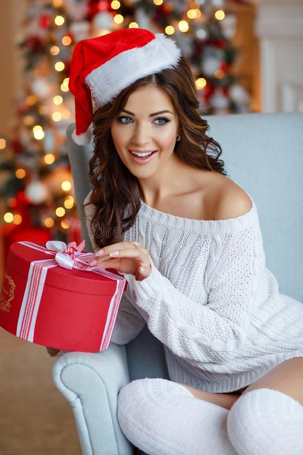 Piękna nikła brunetki dziewczyna w Santa kapeluszu siedzi w wygodnym fotografia royalty free
