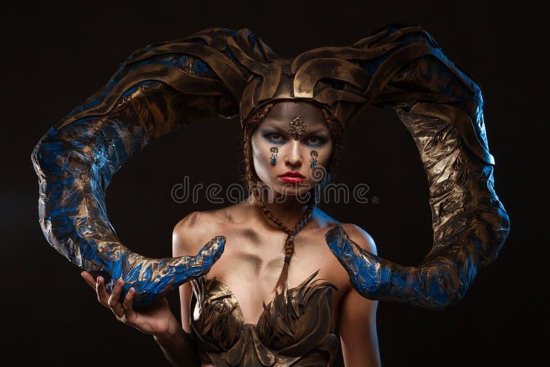 Piękna nikła dziewczyna w kostiumu z rogami dla Halloween na czarnym tle fotografia royalty free