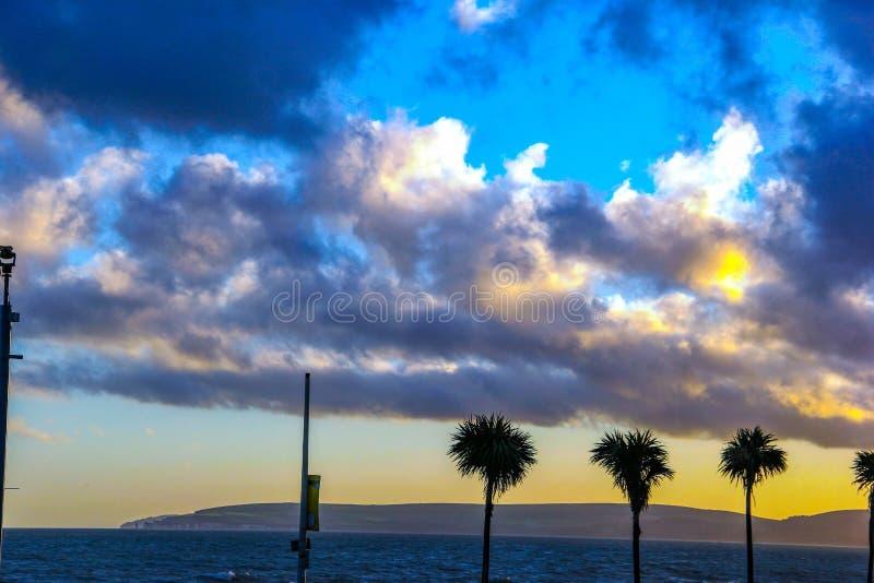 Piękna obłoczna tekstura przy Durdle morza Drzwiową plażą z trzy drzewkami palmowymi obraz royalty free