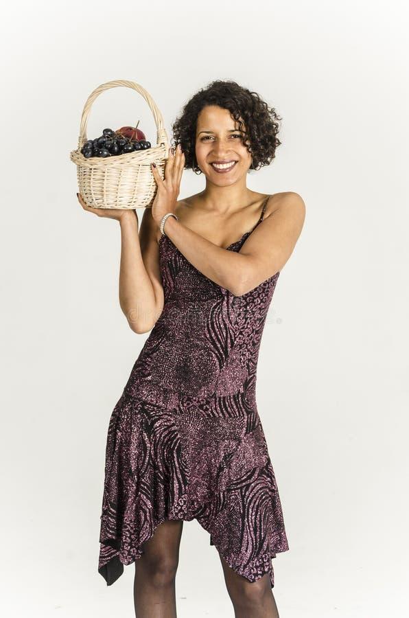 Piękna oliwkowa kobieta w koktajl sukni z koszem owoc zdjęcia royalty free