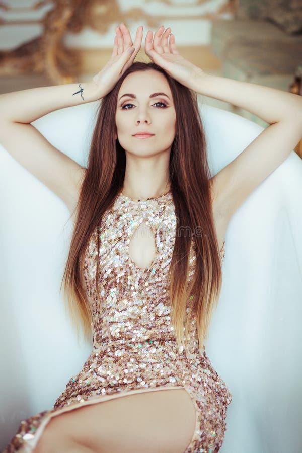 Piękna oszałamiająco młoda kobieta w zadziwiającej błyskotliwość cekinów sukni kłama w białym skąpaniu Jaskrawe pełne wargi, Holl zdjęcia stock