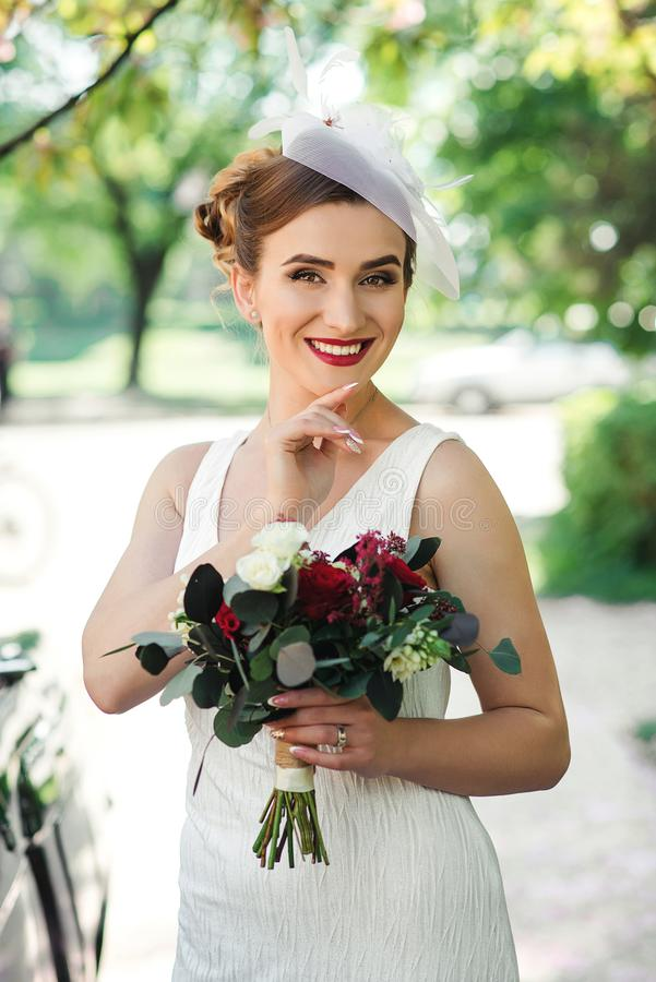 piękna panna młoda Ślubny bukiet w panny młodej ` s rękach pięknych ślicznych fryzury kędziorków wzorcowy portreta profilu ślub M zdjęcia stock