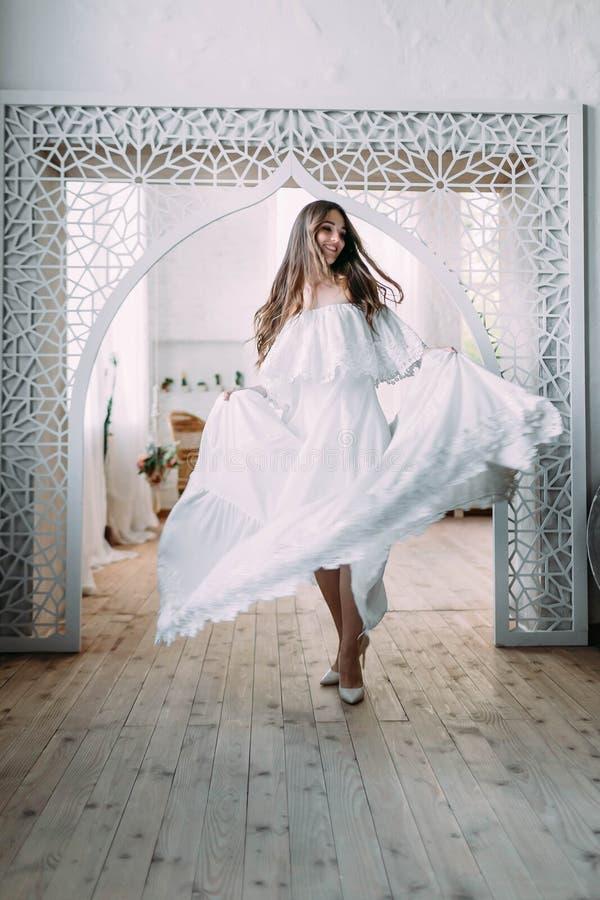 Piękna panna młoda jest przędzalniana wokoło ona w tanu Rozochocona brunetka pozuje w trzepotliwej sukni w roczniku zdjęcie royalty free