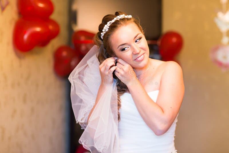 Piękna panna młoda jest ubranym perełkowych kolczyki fotografia stock