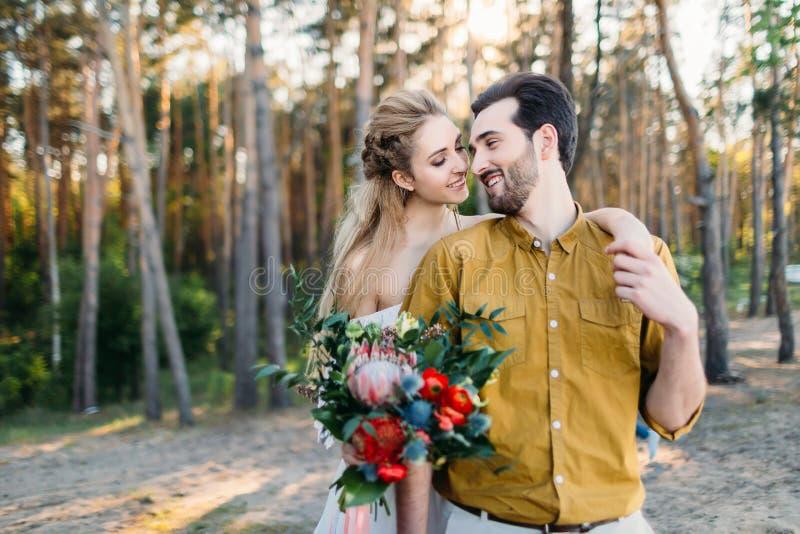 Piękna panna młoda obejmuje jej fornala ramieniem Ślubny spacer w lasowej dziewczynie w bielu mężczyzna w oliwce i sukni zdjęcie royalty free