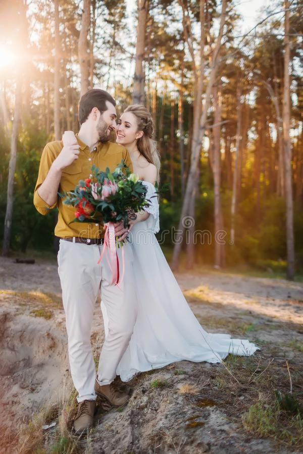 Piękna panna młoda obejmuje jej fornala ramieniem Ślubny spacer w lasu A nowożeńcy spojrzeniach przy each inny dziewczyna wewnątr fotografia royalty free