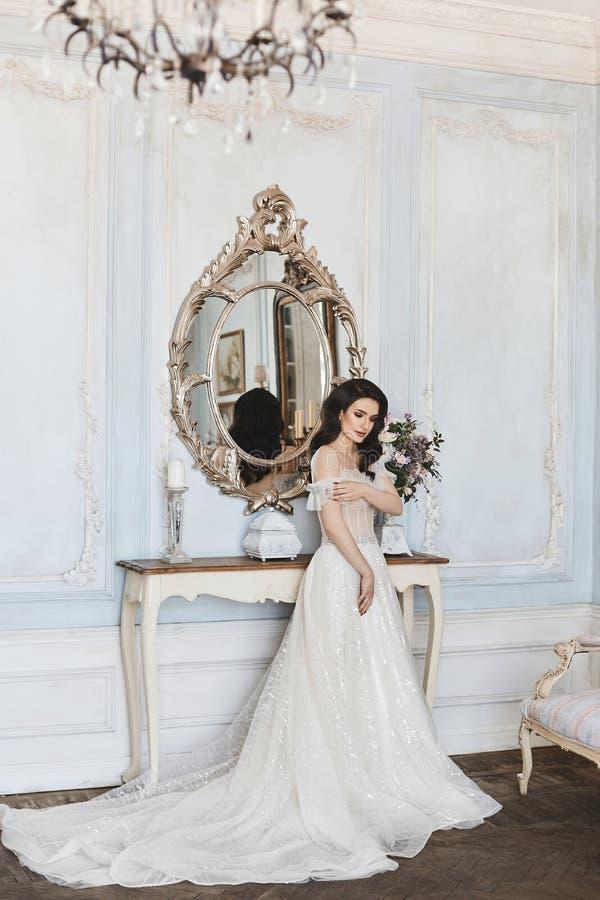 Piękna panna młoda, powabna wzorcowa brunetki dziewczyna w eleganckiej ślub koronki sukni z nagimi ramionami przystosowywa jej su obraz stock