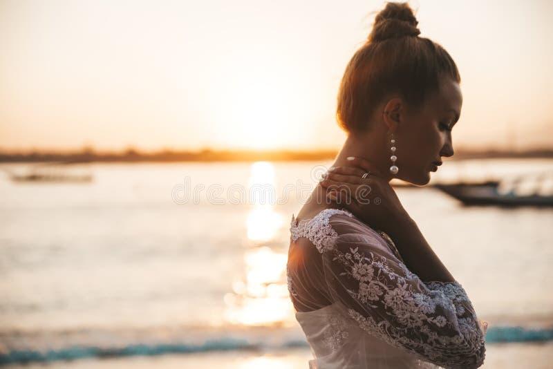 Piękna panna młoda pozuje na plaży za morzem przy zmierzchem obraz royalty free