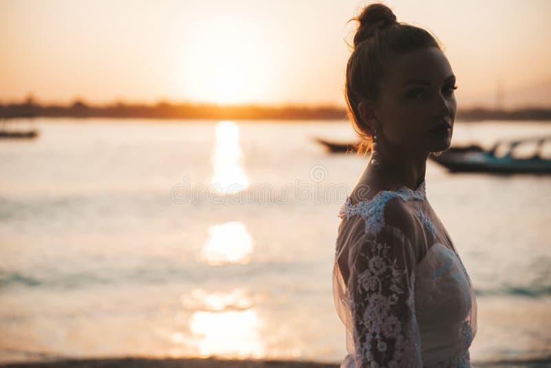 Piękna panna młoda pozuje na plaży za morzem przy zmierzchem fotografia stock