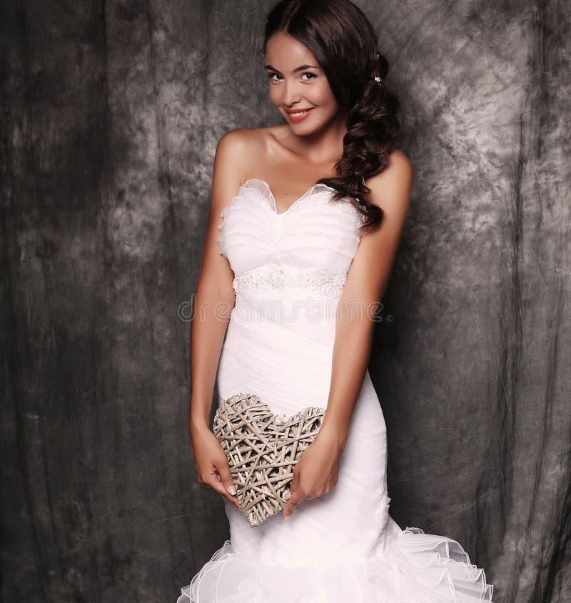 Piękna panna młoda trzyma dekoracyjnego serce w ślubnej sukni zdjęcie stock