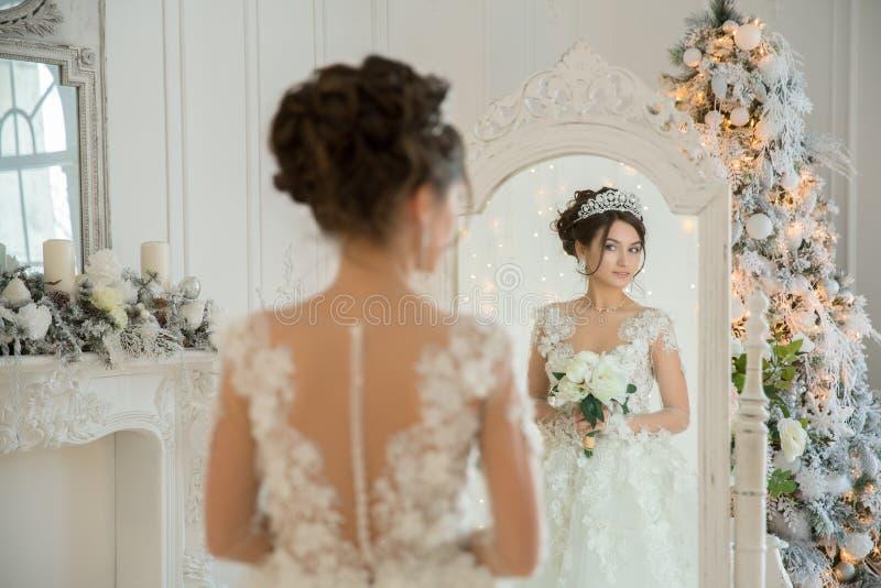 Piękna panna młoda w ślubnej sukni przy lustrem w bożych narodzeniach Gira obrazy royalty free