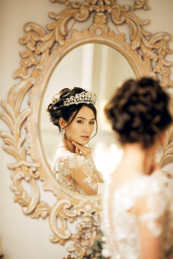 Piękna panna młoda w ślubnej sukni przy lustrem w bożych narodzeniach Gira zdjęcie stock