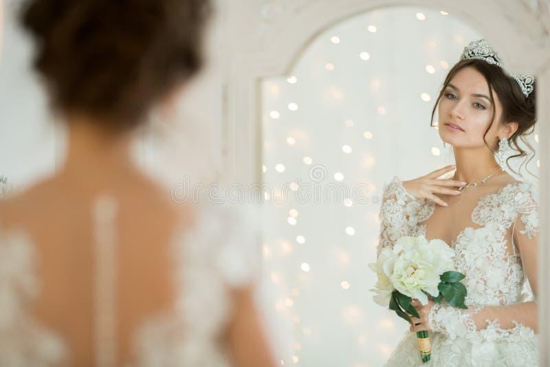 Piękna panna młoda w ślubnej sukni przy lustrem w bożych narodzeniach Gira fotografia stock