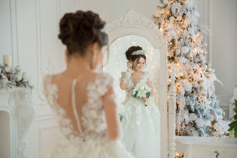 Piękna panna młoda w ślubnej sukni przy lustrem w bożych narodzeniach Gira fotografia royalty free