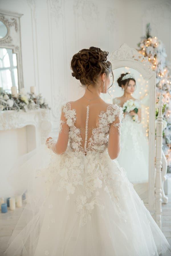 Piękna panna młoda w ślubnej sukni przy lustrem w bożych narodzeniach Gira obraz stock