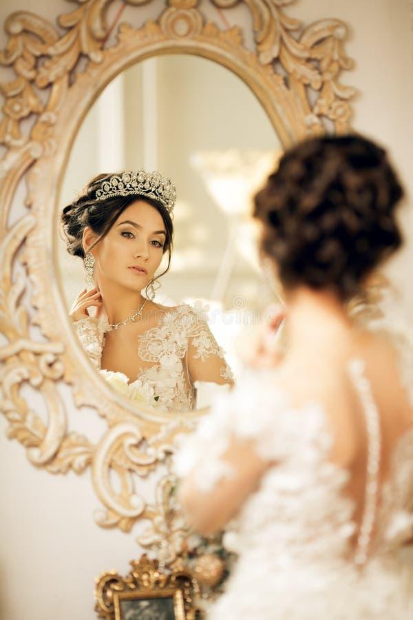 Piękna panna młoda w ślubnej sukni przy lustrem w bożych narodzeniach Gira obrazy stock